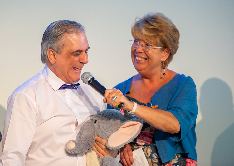 Woman smiling and holding microphone up to a man in bow tie who is also smiling.
